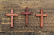 three wooden cross on a wood floor