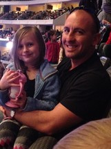A father and toddler daughter sitting in a theater for Disney on Ice