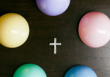 Cross surrounded by colorful Easter eggs.