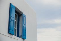 blue shutters on a white house in Greece