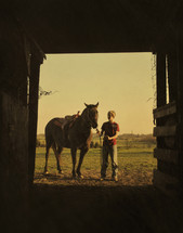 Teen boy bringing horse to stall