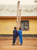 two young boys leaning on a tree trunk