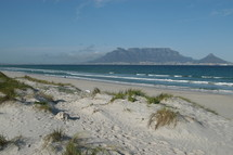 Dunes on a white sand beach in front of  Table Mountain