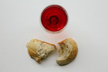 Broken bread and a glass of wine.
