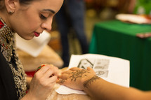 a woman painting henna tattoos