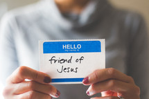 woman holding a name tag with the word friend of Jesus