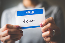 woman holding a name tag with the word fear