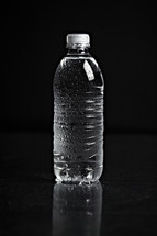 A refreshing bottle of water on black seamless