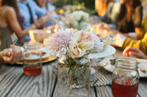 Friends sharing a meal together at a picnic table, with a mason jar of flowers and tea, outside.
