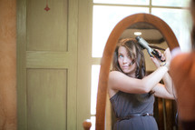 woman curling her hair with a curling iron in a mirror
