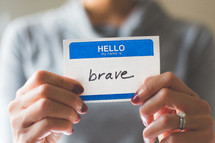 woman holding a name tag with the word brave