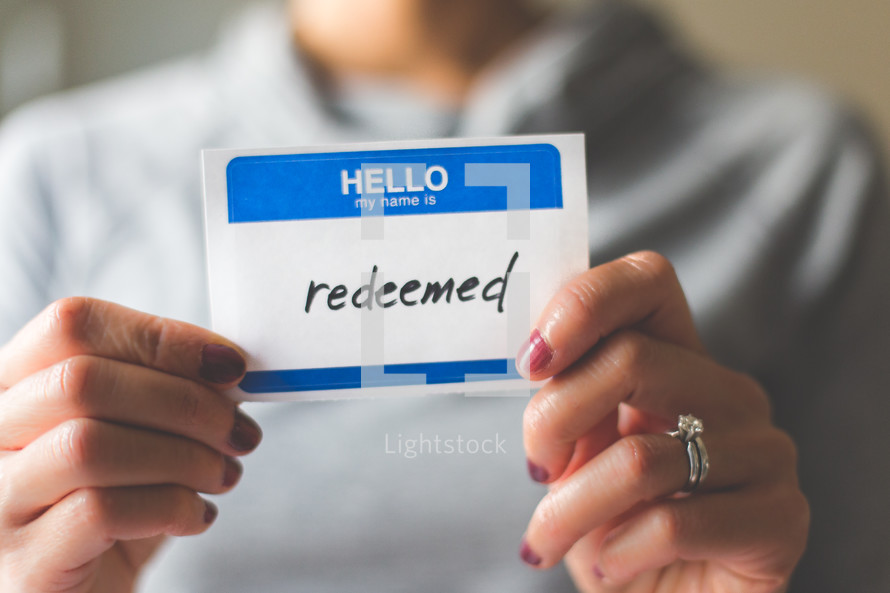 woman holding a name tag with the word redeemed