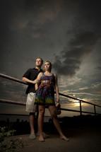 Couple standing on bridge at sunset