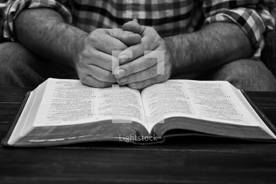 a man in a plaid shirt with praying hands over the pages of a Bible