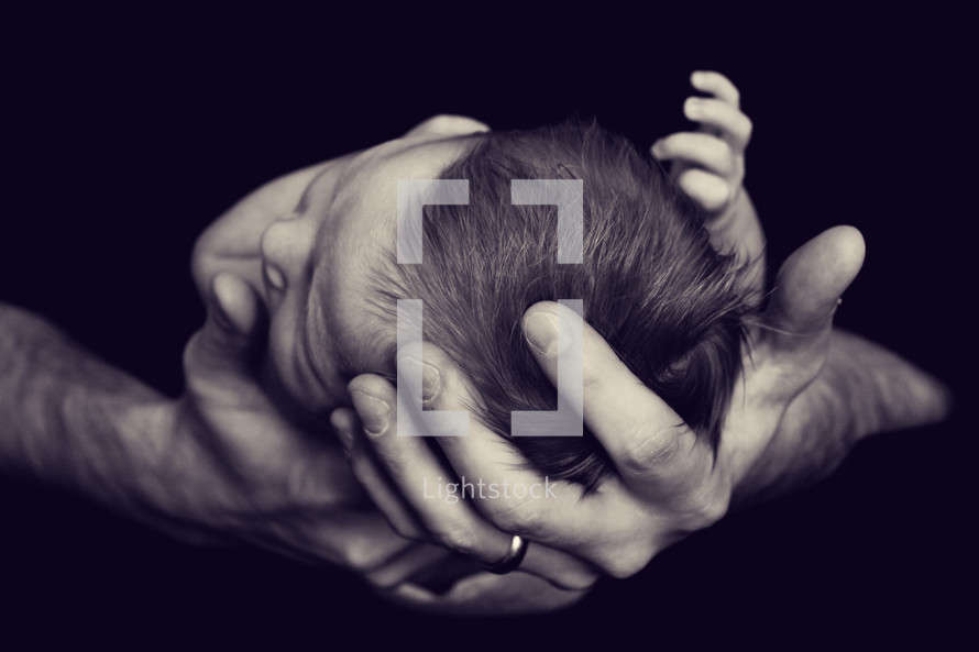 newborn baby in father's hands
