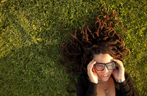 Woman lying on green grass with glasses