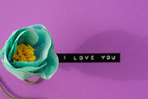 """I love you,"" on a purple background with a turquoise flower."