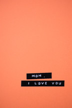 "A label reading, ""Mom, I love you,"" on an orange background."