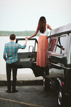 a couple holding hands beside a VW van