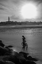 man with a bicycle on a beach and a distant lighthouse