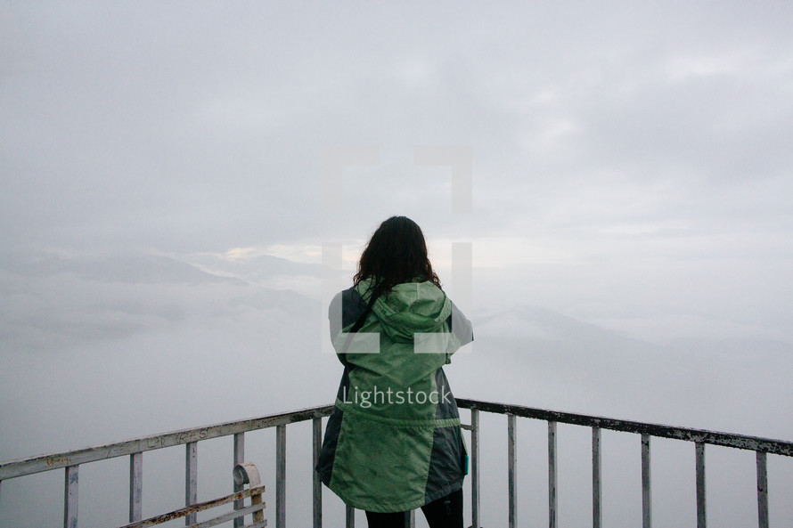 a woman looking out over a railing at mountains in the distance