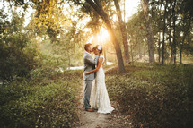 groom kissing his bride on the forehead standing on an outdoor path