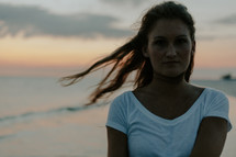 a young woman walking on a beach at sunset