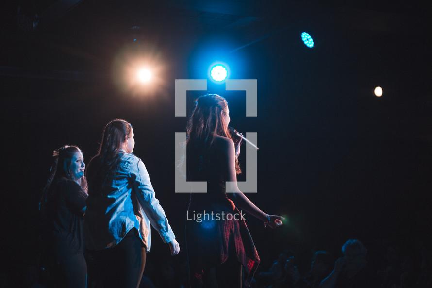 women singing on stage