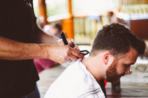 a man getting a haircut at a barbers shop