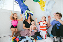 blank stare from a mother as children toss clothes in the air