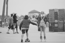a couple holding hands skateboarding and roller blading on a boardwalk