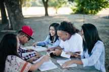 friends reading Bibles together outdoors at a picnic table