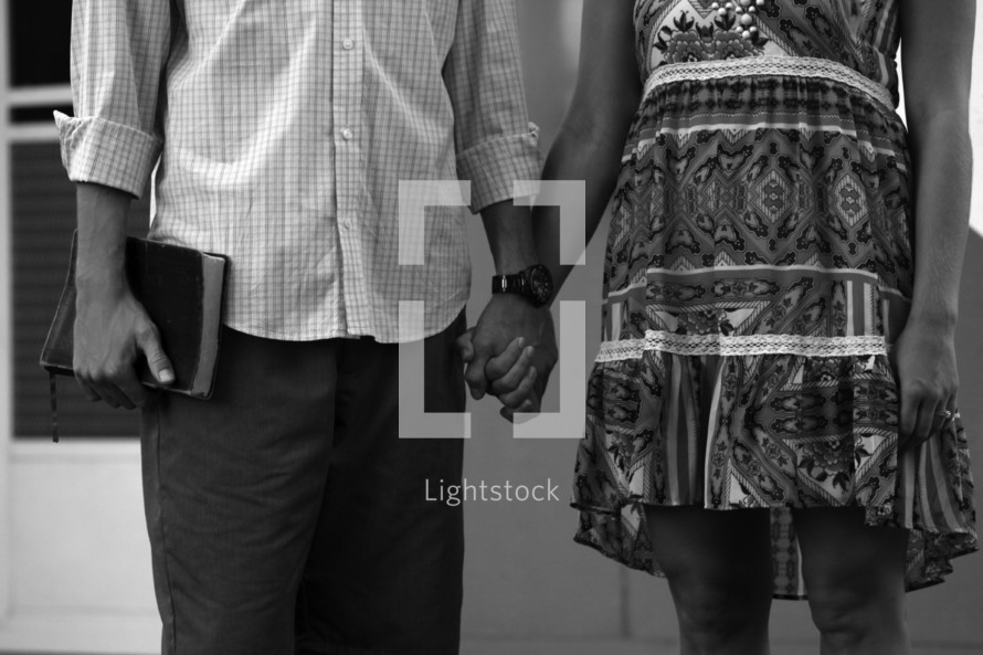 a couple holding hands and carrying a Bible