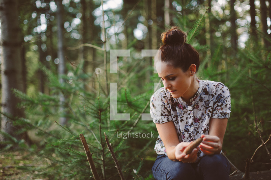 woman alone sitting in a forest thinking