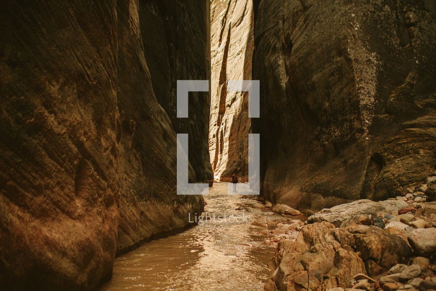 woman walking through a river at the bottom of a canyon