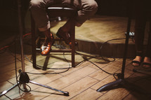 man sitting on a stool and microphone stands