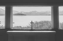 A cross in a window with a view of a lake and mountains.