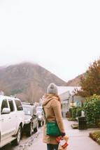 A woman in winter clothes stands on a sidewalk in a mountain town.