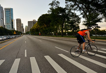man riding a bike across a city crosswalk