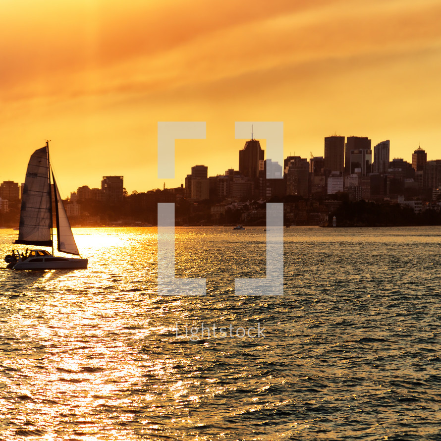 sailing in a harbor at sunset