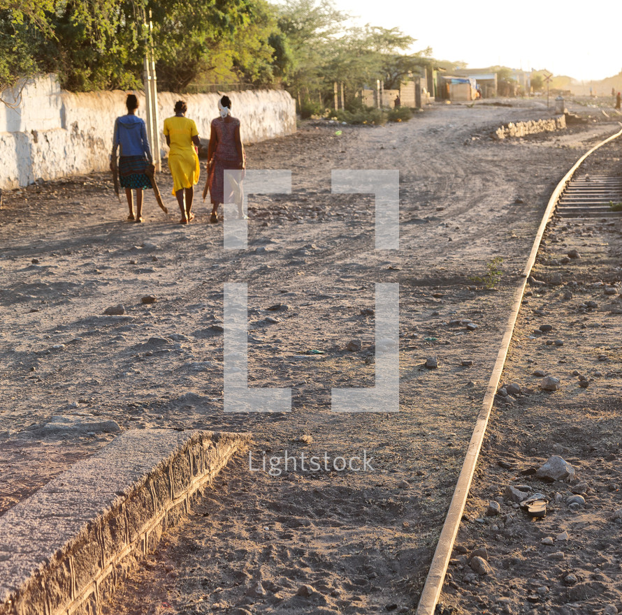 women walking on a dirt road next to tracks in Africa