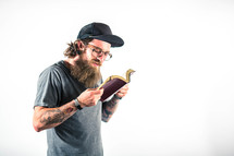 man with tattoos reading a Bible
