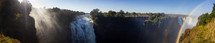 water flowing over Victoria falls and a rainbow