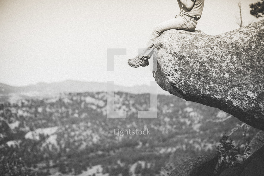 Man sitting on the edge of a cliff.