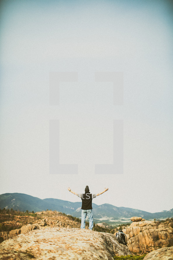 Man standing with open arms on a rocky hill.