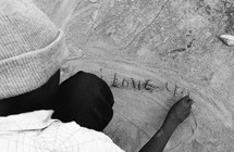 man writing I LOVE YOU in sand