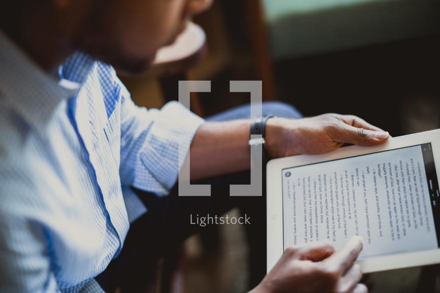 man reading a Bible on an iPad screen