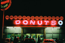 People shopping at a donut shop at night.