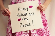 A Little girl holding up a sign that read's Happy Valentine's Day Jesus