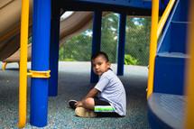 child sitting under a slide on a playground
